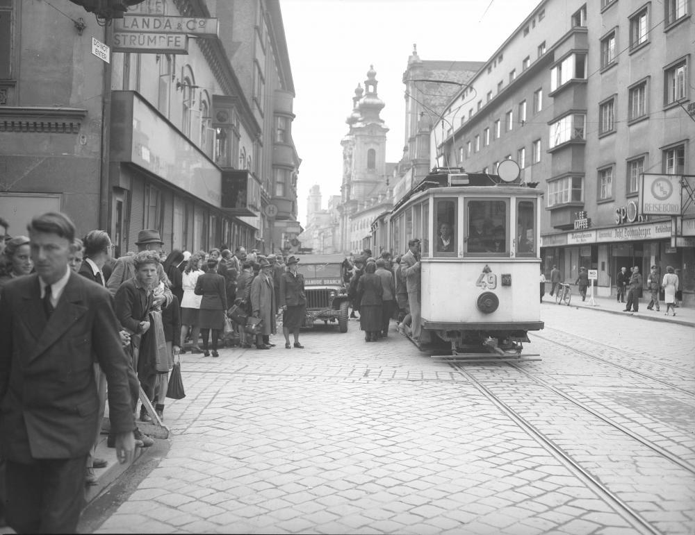 Im Juli übergab die US-Armee Teile Oberösterreichs an die sowjetische Armee. Zu dieser Zeit soll diese Aufnahme den Erfolg der US-Verwaltung unterstreichen: Das US-kontrollierte Linz erscheint als urbanes Zentrum – Leben und Verkehr wurden wieder hergestellt, vom Krieg ist nichts zu sehen.