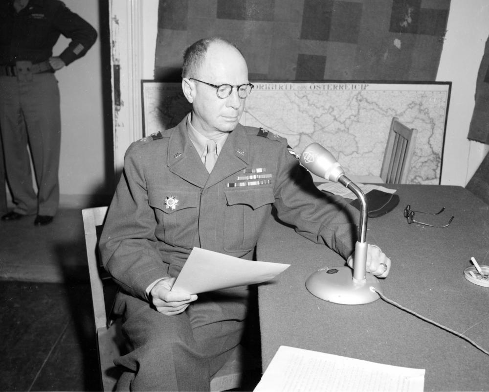 """US-General Robertson hält die Eröffnungsansprache für den US-kontrollierten Rundfunksender """"Rot-Weiß-Rot"""" im Salzburger Sendestudio. Die sowjetische Auszeichnung an der Uniform betont das Einvernehmen zwischen den alliierten Mächten."""